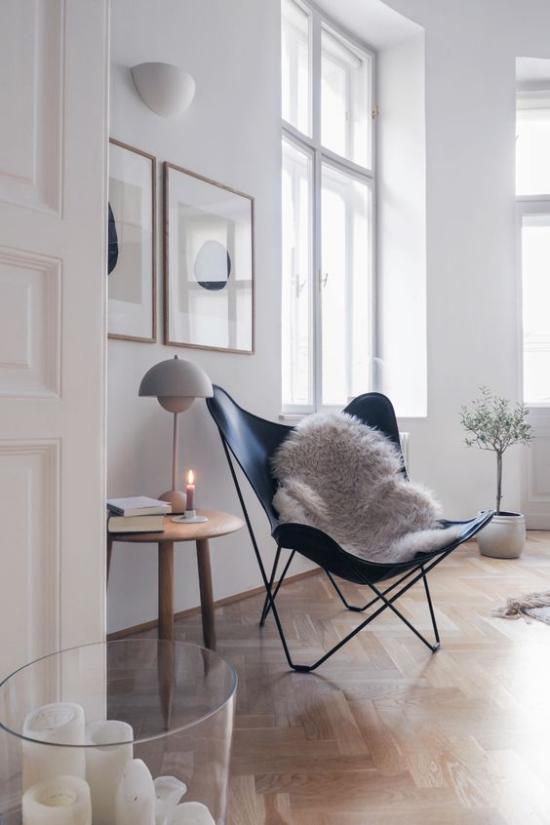 Wohnzimmer optisch erweitern helle Farben Weiß dominiert viel Tageslicht helles Parkett Klappstuhl weißer Pelz