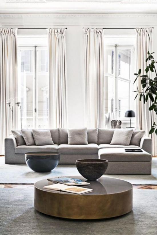 Wohnzimmer optisch erweitern helle Möbel interessante Deko Artikel als Blickfang viel natürliches Licht weite Fenster weiße Gardinen