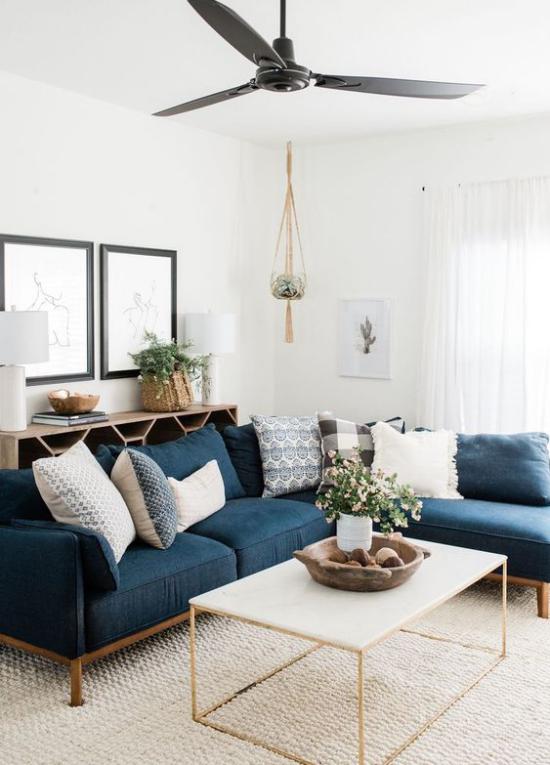Wohnzimmer optisch erweitern weiß und dunkelblau im Kontrast viel Tageslicht keine Grenzen dunkles Sofa als Akzent