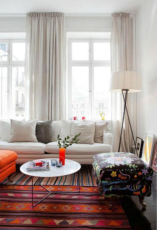 Wohnzimmer optisch erweitern weißes Sofa weiße Gardinen viel Tageslicht bunter Teppich Orange dominiert