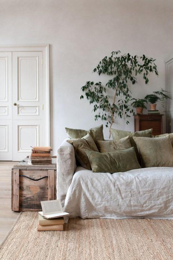 Zeitgemäße Raumgestaltung helle Farben Sofa Teppich olivgrüne Deko Kissen eine Grünpflanze