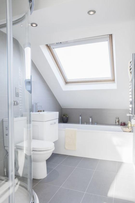 Zeitgemäße Raumgestaltung helles Badezimmer ganz in Weiß Badewanne unter der Dachschräge Duschecke hinter Glaswand