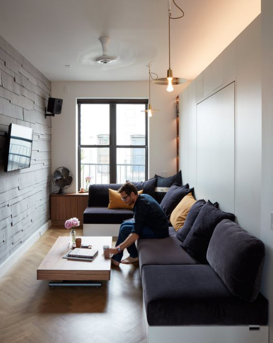Zeitgemäße Raumgestaltung modernes enges Wohnzimmer dunkellila Ecksofa Fernseher an der Ziegelwand