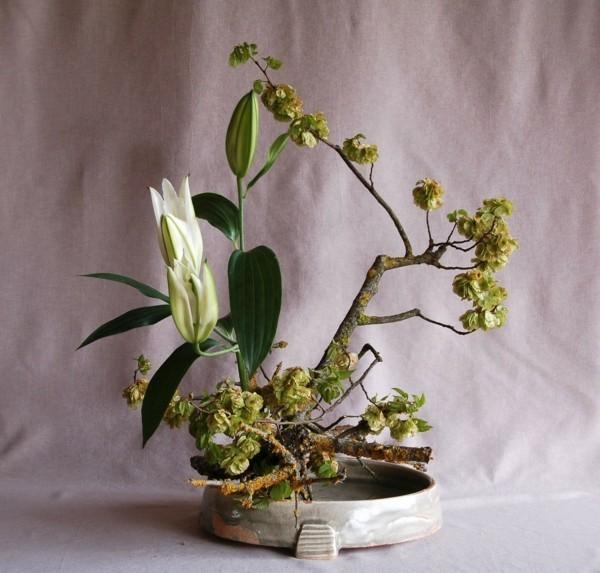 weiße lilie zweige moos ikebana