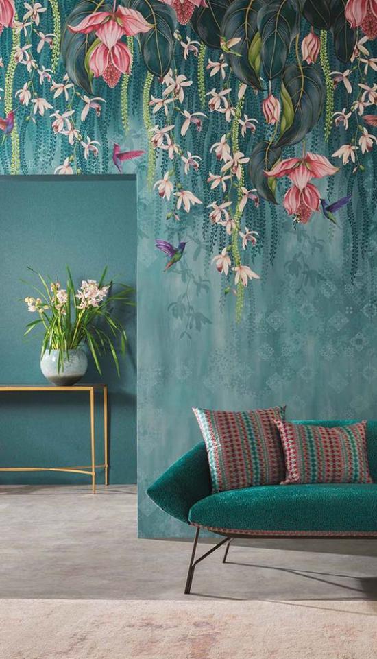 Blumentapeten Deko Trend 2020 Wohnzimmer blaugrauer Hintergrund türkisfarbenes Sofa üppige Blumen weiße Vase mit Blumen