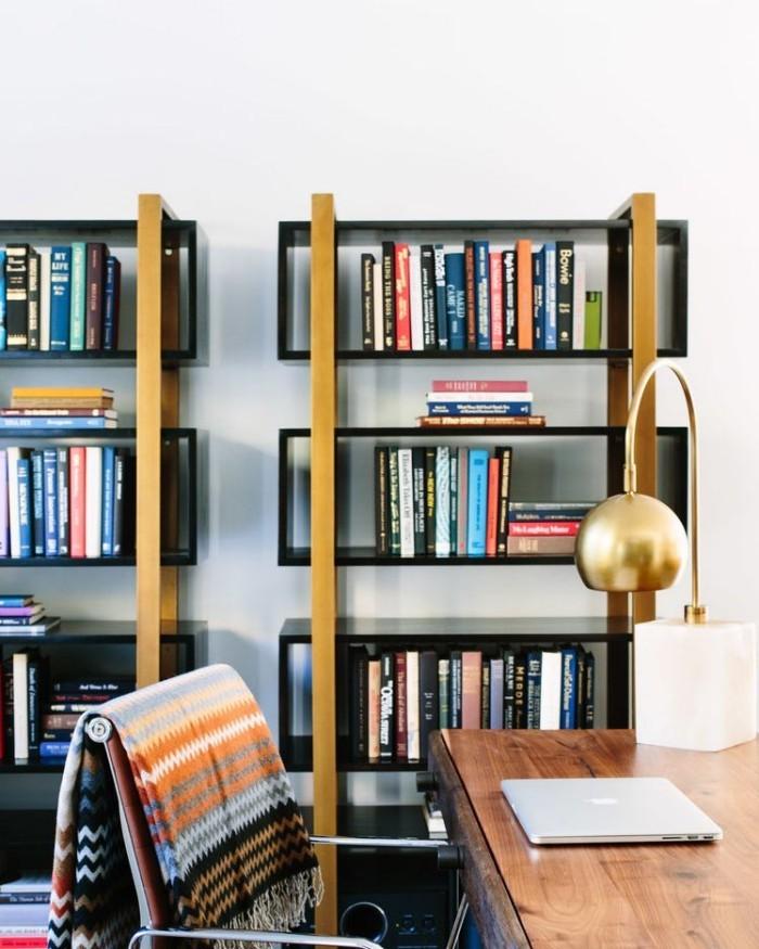 Geheimnisse des Innendesigns enthüllt Bücherregal bunte Bücher Bogenlampe Holztisch zum Lesen Alt und Neu in Kombination