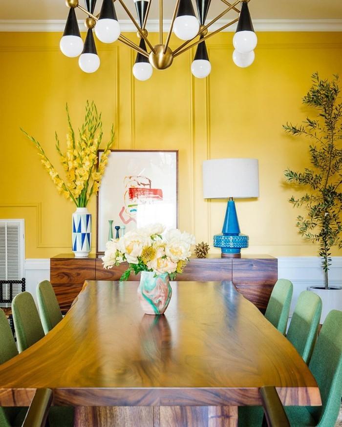 Geheimnisse des Innendesigns enthüllt Esszimmer in warmem Sonnengelb ausgeführt gelbe Wand hellgrüne Stühle gelbe Gladiolen in großer Vase