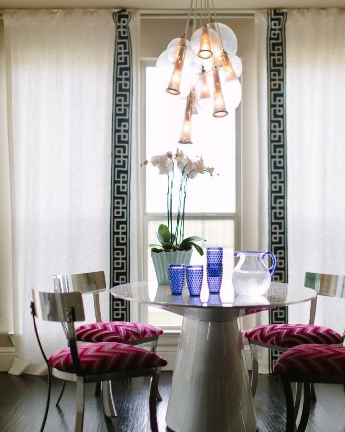 Geheimnisse des Innendesigns enthüllt einladende kleine Essecke vor dem Fenster runder weißer Tisch Topf mit Orchideen ausgefallene Hängeleuchte