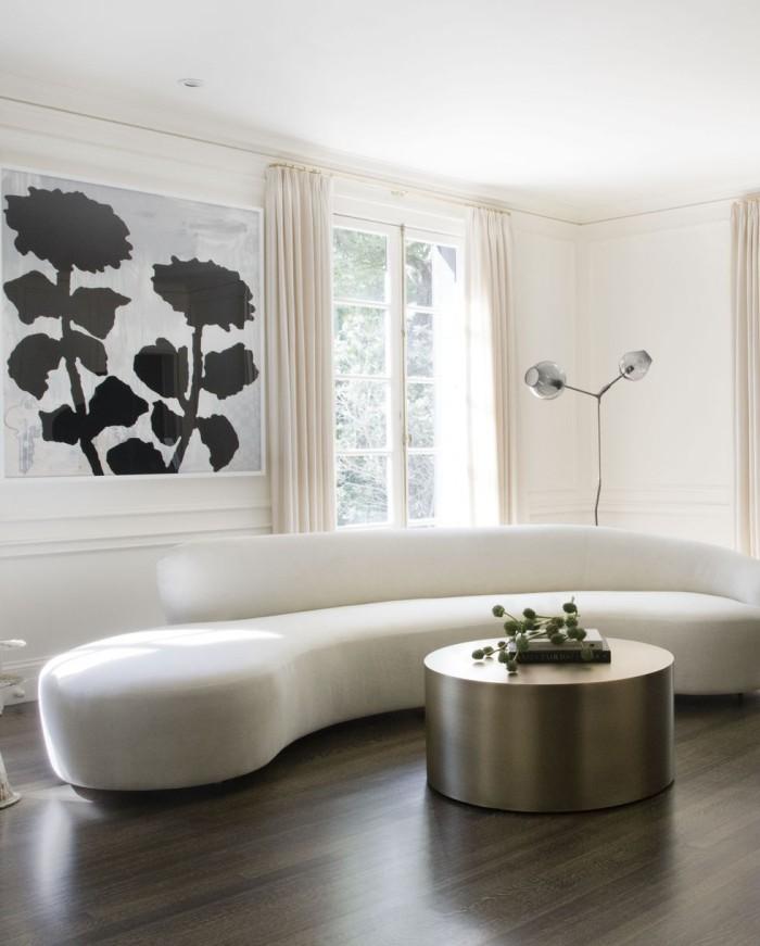 Geheimnisse des Innendesigns enthüllt elegant eingerichtetes Wohnzimmer runde weiße Couch runder Kaffeetisch im Metallglanz dunkler Boden als Kontrast