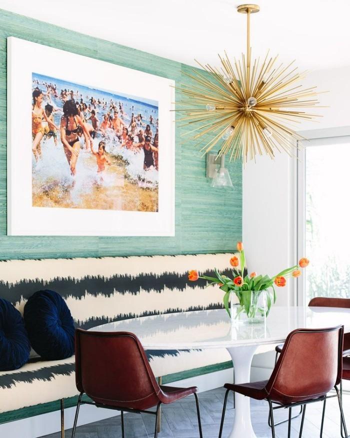 Geheimnisse des Innendesigns enthüllt elegant gestaltetes Esszimmer weißer Esstisch Sitzbank dunkelblaue Kissen moderne Hängeleuchte Wandbild