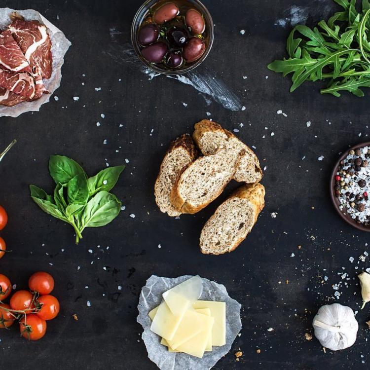 Gesundes und ausgewogenes Essen in Zeiten der Corona-Krise Brot Käse Oliven Fleisch Tomaten Basilikumblätter
