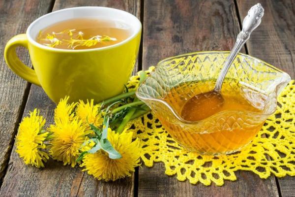 Löwenzahn gelbe Blüten Blätter Tasse Löwenzahntee kleine Schüssel mit Honig daneben