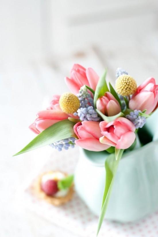 Osterdeko in Pastellfarben Blumen in zarten Farbtönen in Vase bringen eine fröhliche Note mit auf den Ostertisch