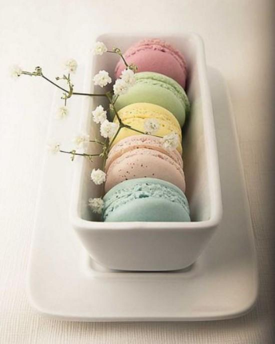 Osterdeko in Pastellfarben Maccarons in Pastelltönen sehen lecker aus weiße Blüten als Schmuck im weißen Geschirr