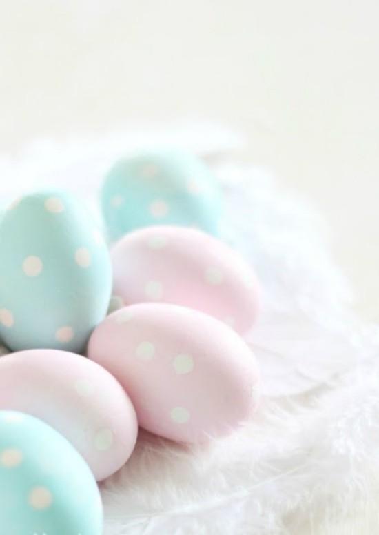 Osterdeko in Pastellfarben Ostereier in Hellblau und Rosa mit weißen Punkten auf weichem Grund