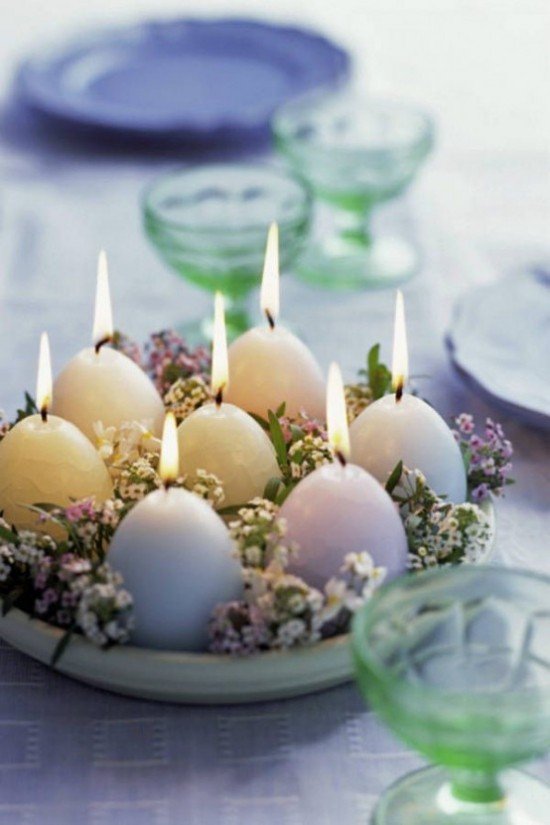 Osterdeko in Pastellfarben angezündete Kerzen in Pastelltönen dazwischen zarte Blüten gelegt