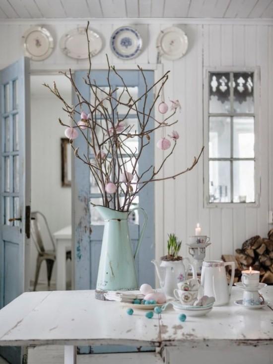 Osterdeko in Pastellfarben im rustikalen Stil Tisch ländlich dekoriert Gießkanne mit Zweigen und Pompons