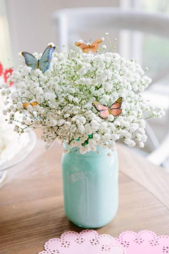 Osterdeko in Pastellfarben weiße Blüten von der Wiese im Glas als Blickfang Schmetterling