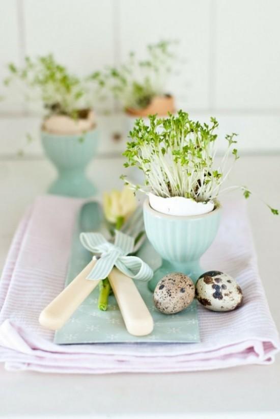 Osterdeko in Pastellfarben zwei Ostereier Blumenbehälter in Himmelblau mit grünen Kräutern und Gras bepflanzt