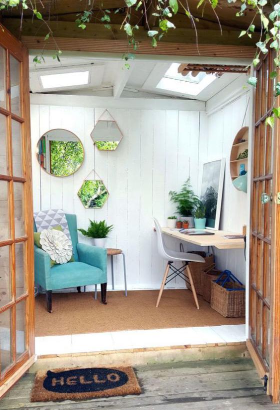 Outdoor - Trends 2020 Gartenhaus als praktisches Heimbüro eingerichtet Tisch Stuhl blauer Sessel Wandspiegel