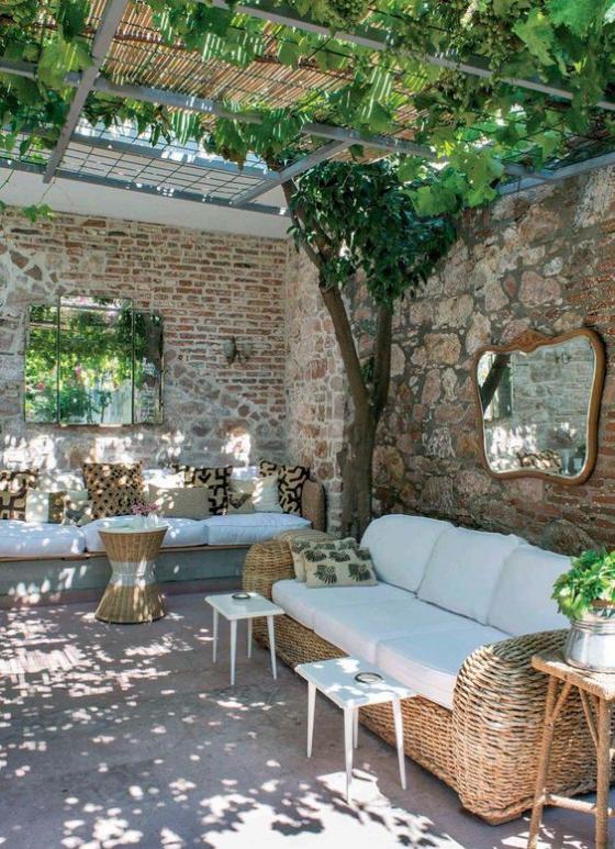 Outdoor - Trends 2020 gemütliches Wohnzimmer im Freien Steinwand als Sichtschutz bequeme Flechtmöbel