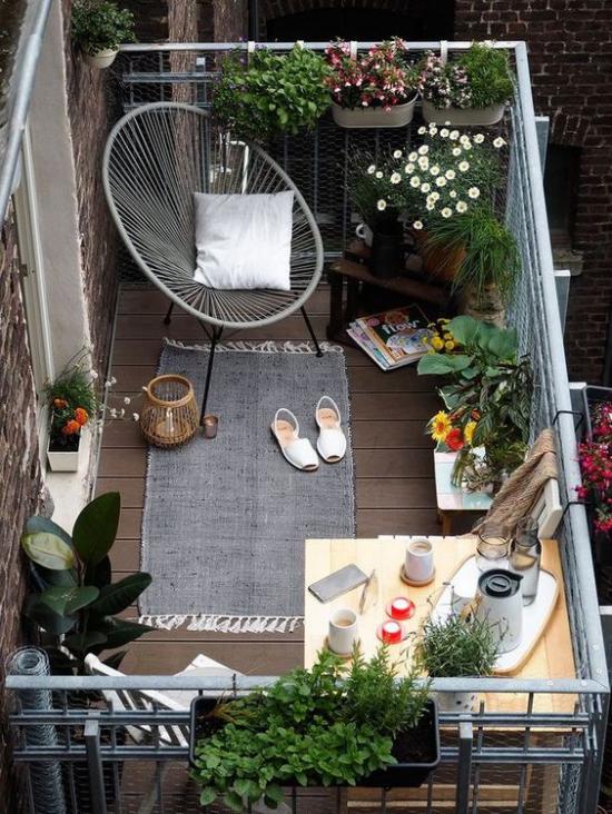 Terrasse frühlingsfit machen Ideen auch für kleinen Balkon frühlingshaft gestalten schöne Blumen Sessel aus Metall grauer Teppich