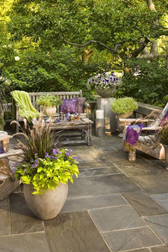 Terrasse frühlingsfit machen alte Holzmöbel Behälter mit Blumen und Grünpflanzen