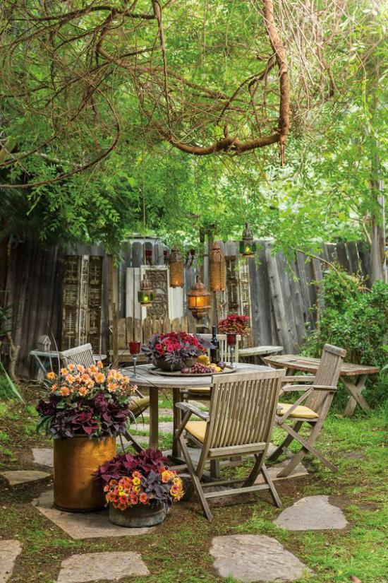 Terrasse frühlingsfit machen alte Holzmöbel und Accessoires mixen Blumen hängende Laternen