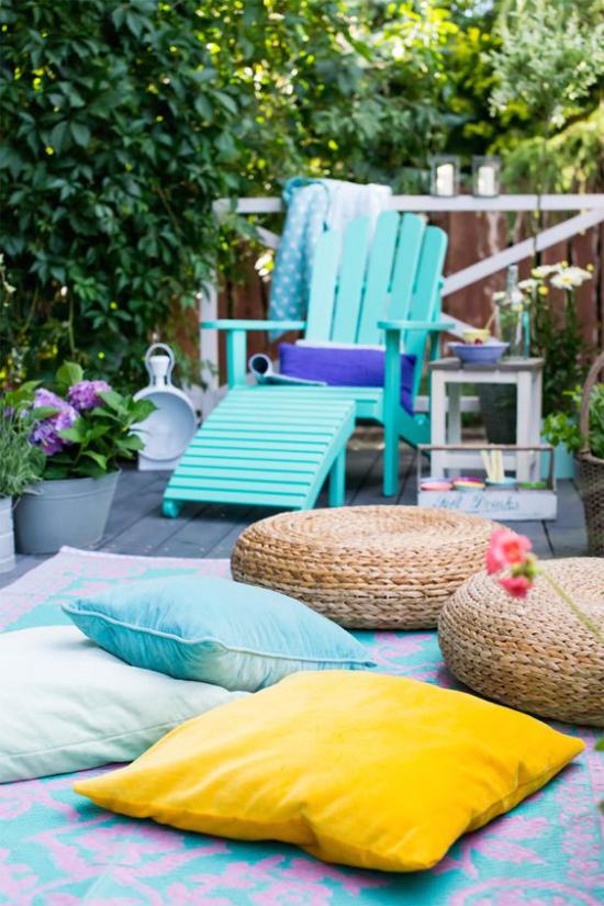 Terrasse frühlingsfit machen hellblaue Liege aus Holz viele bunte Sitzkissen hellblau gelb geflochten angenehme Atmosphäre