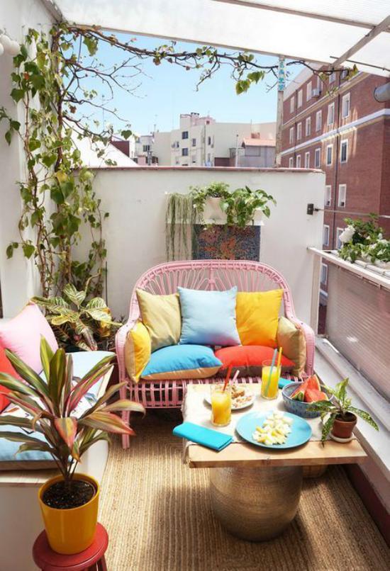 Terrasse frühlingsfit machen kleinen Balkon gestalten kleine Sofas runder Tisch viele Blumen bunte Kissen frühlingshafte Stimmung