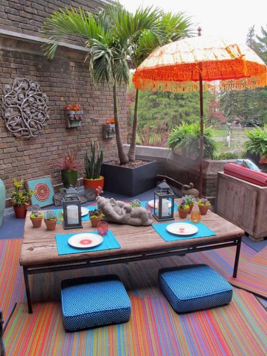 Terrasse frühlingsfit machen kunterbunte Wohnaccessoires und Deko viel Charme hohe Palme Sonnenschirm