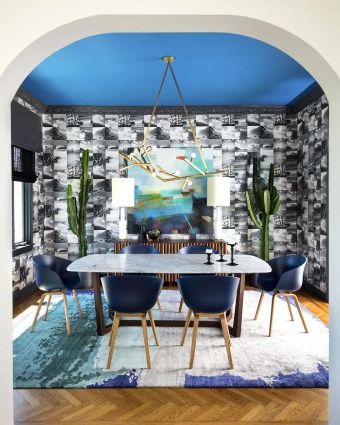attraktive Wandgestaltung Tapete in Steinoptik blaue Zimmerdecke Stühle weißer Esstisch Teppich