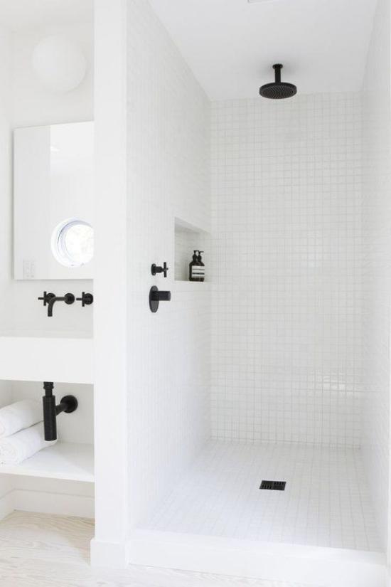 Badezimmer ganz in Weiß Badarmatur in Schwarz farbige Akzente durchbrechen die Eintönigkeit