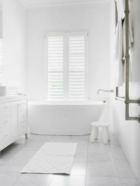 Badezimmer ganz in Weiß Badewanne vor dem Fenster Sichtschutz viel natürliches Licht kleiner Hocker