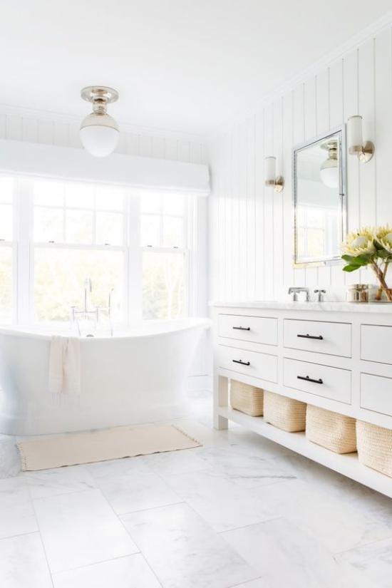Badezimmer ganz in Weiß Blumen auf dem Waschtisch Spiegel Badewanne vor dem Fenster viel natürliches Licht