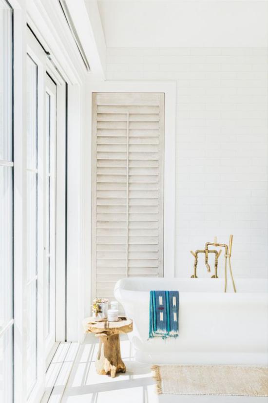 Badezimmer ganz in Weiß Holzhocker vor dem Fenster betont den Vintage Look
