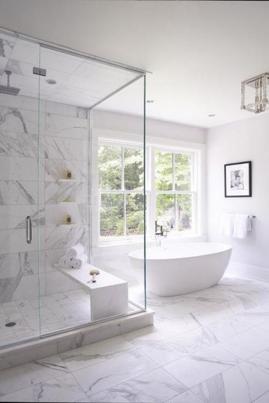 Badezimmer ganz in Weiß Marmorfliesen viel natürliches Licht freistehende Badewanne Dusche Glaswände