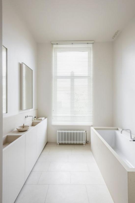 Badezimmer ganz in Weiß Minimalismus herrscht schmaler Raum sehr elegant gestaltet Fenster Spiegel Waschtisch