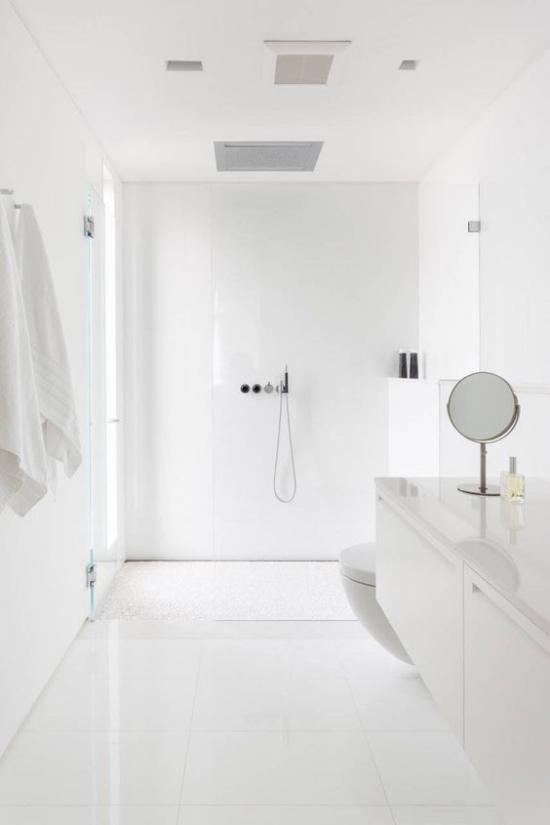 Badezimmer ganz in Weiß Minimalismus pur weiße Tücher kleiner runder Spiegel