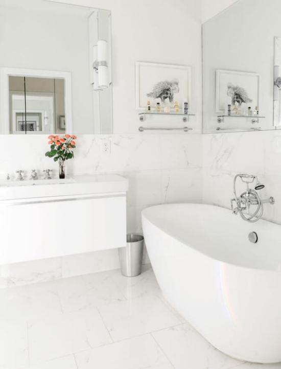 Badezimmer ganz in Weiß Vase rosa Rosen auf dem Waschtisch Badewanne rechts zwei Wandspiegel