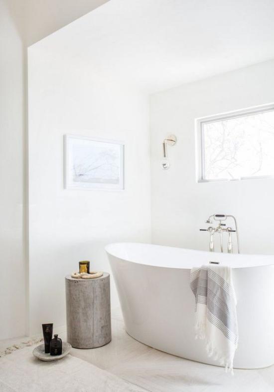 Badezimmer ganz in Weiß freistehende Badewanne Baumstamm als Blickfang viel natürliches Licht