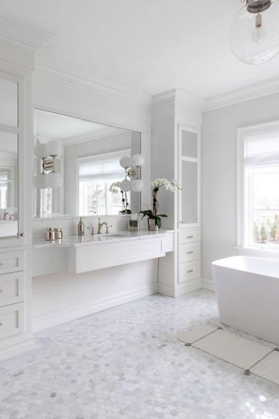 Badezimmer ganz in Weiß geräumig weiter Waschtisch großer Wandspiegel weiße Schränke Lampen Fliesen Blumen