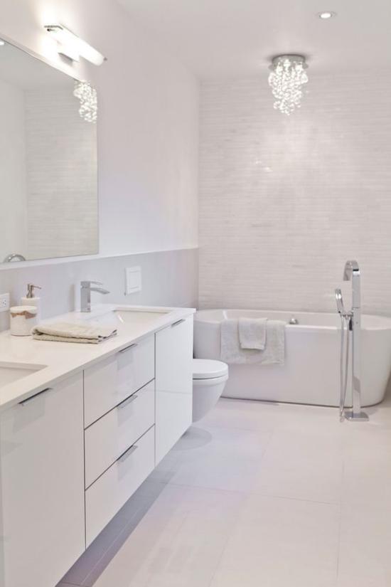 Badezimmer ganz in Weiß künstliche Beleuchtung Spiegellampe Deckenstrahler kleiner Kronleuchter Blickfang