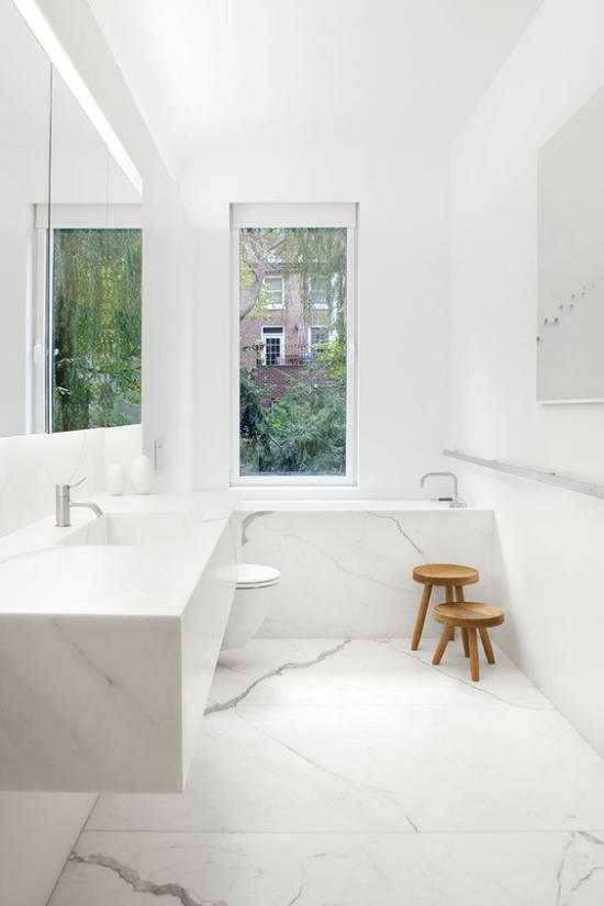 Badezimmer ganz in Weiß kleine Holzhocker als besondere Hingucker Marmorfliesen