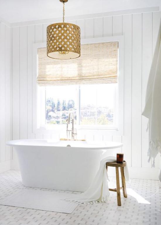 Badezimmer ganz in Weiß schöne freistehende Badewanne vor dem Fenster viel Licht Rollos zum Schichtschutz