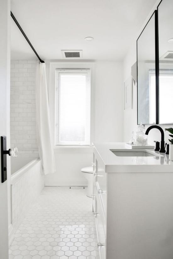 Badezimmer ganz in Weiß weiße Metro Fliesen an der Wand andere Form auf dem Boden schwarze Armaturen Fenster viel natürliches Licht
