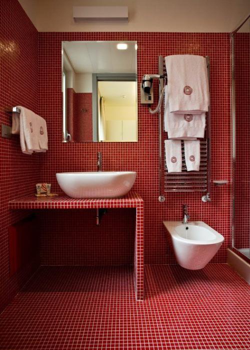 Badezimmer in Rot Wände Boden Waschtisch mit kleinen roten Fliesen bedeckt weißer Mörtel WC Waschbecken Handtücher weiß Wandspiegel