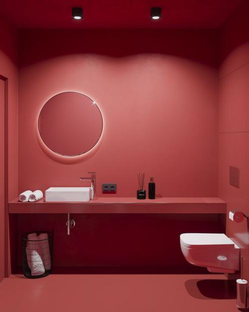 Badezimmer in Rot WC weiß Waschtisch Waschbecken weiß Handtücher alles andere rot coole Beleuchtung runder Spiegel