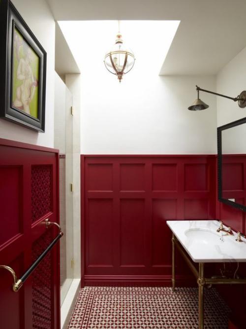 Badezimmer in Rot dunkelrote Wandvertäfelung weißer Waschtisch rechts Spiegel Leuchte links Wandbild