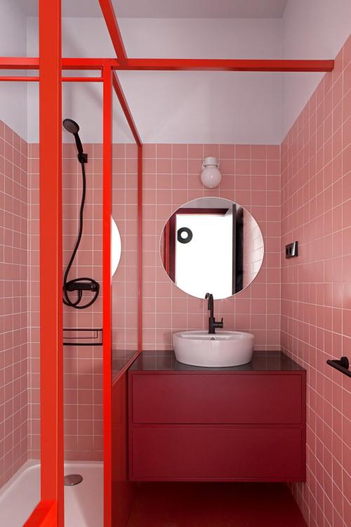 Badezimmer in Rot roter Waschtischschrank rosa Fliesen runder Spiegel Duschecke